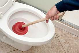 A REDLANDS plumber uses a plunger to unclog a toilet.
